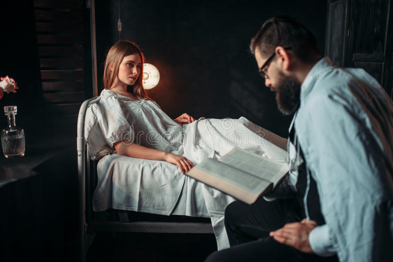 Man reading book against ill woman in hospital bed stock photo