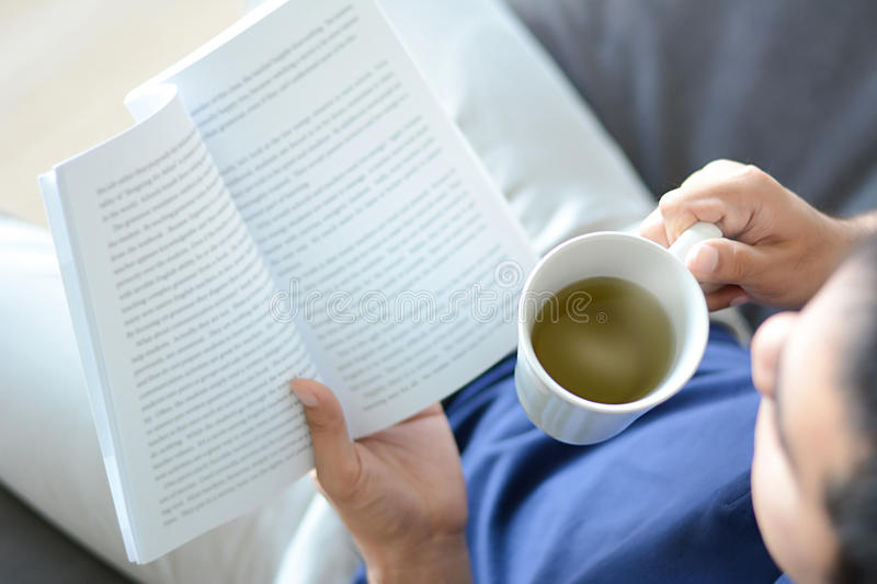 A man reading book with hot tea cup in another hand stock photo