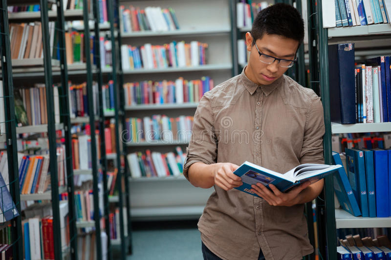 Man reading book in library. Portrait of a handsome man reading book in library stock image