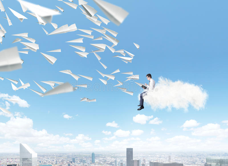 Man reading book. Man sitting on pile of books reading, paper planes flying from book. Blue sky and city at background. Paris. Concept of reading stock photo