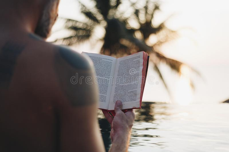 Man reading a book in the swimming pool royalty free stock photos