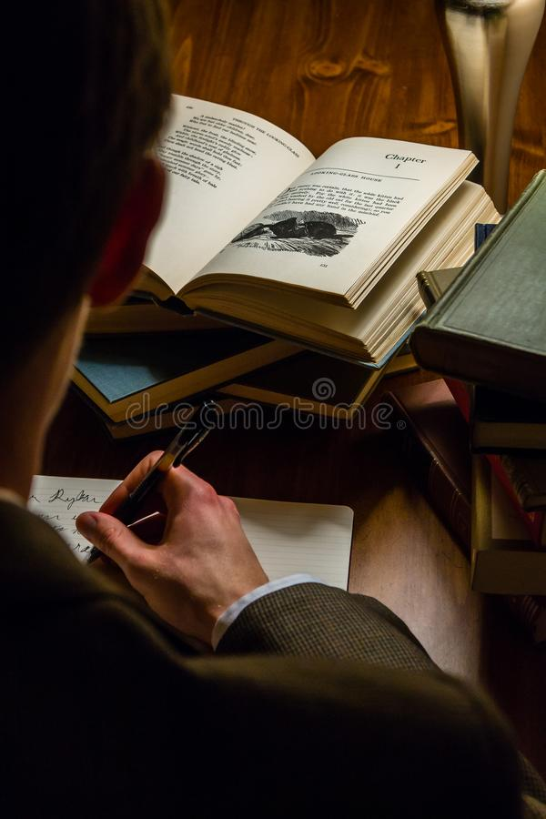 Man reading a book and taking notes royalty free stock photography