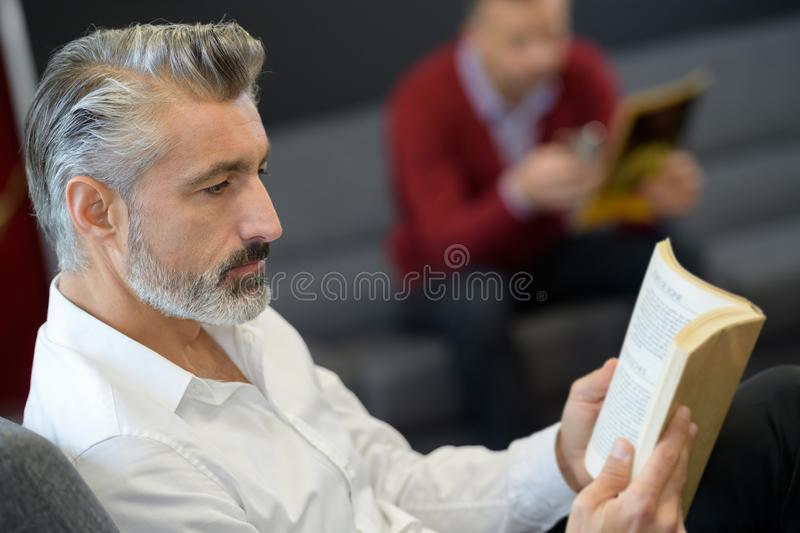 Man reading book in waiting room royalty free stock photo