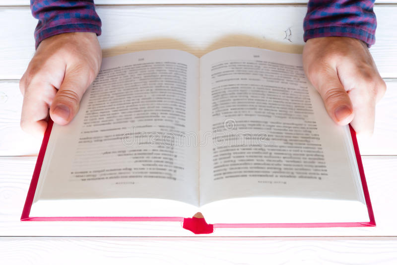 Man reading a book on a white wooden background stock image