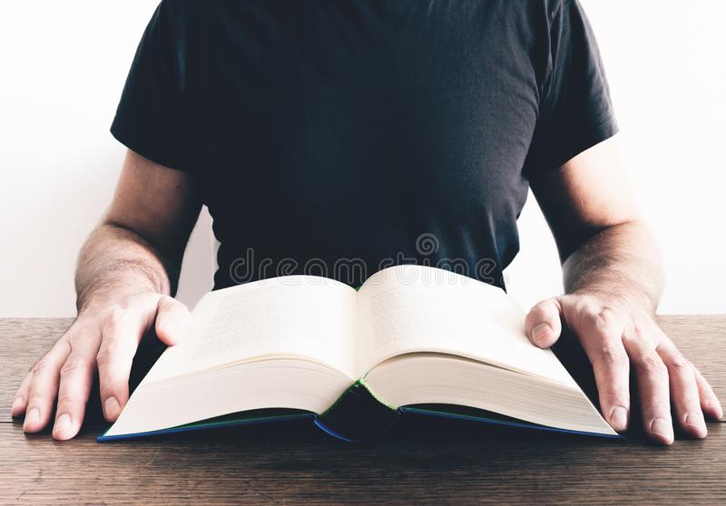 Man reading book at wooden table stock photography