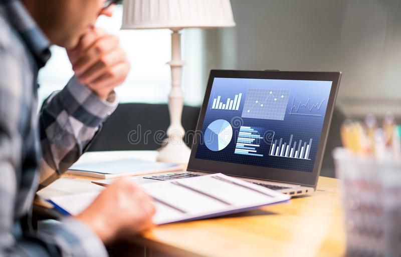Man reading business report paper. Laptop with financial graphs stock photos