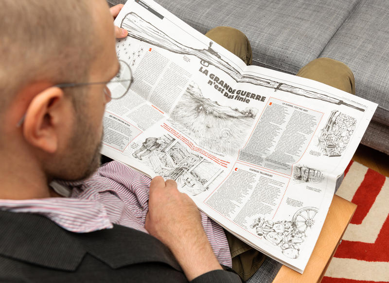 Man reading Charlie Hebdo reading article about war. PARIS, FRANCE - NOV 12, 2016: Man reading Charlie Hebdo magazine on after Donal Trump elections as USA royalty free stock photos
