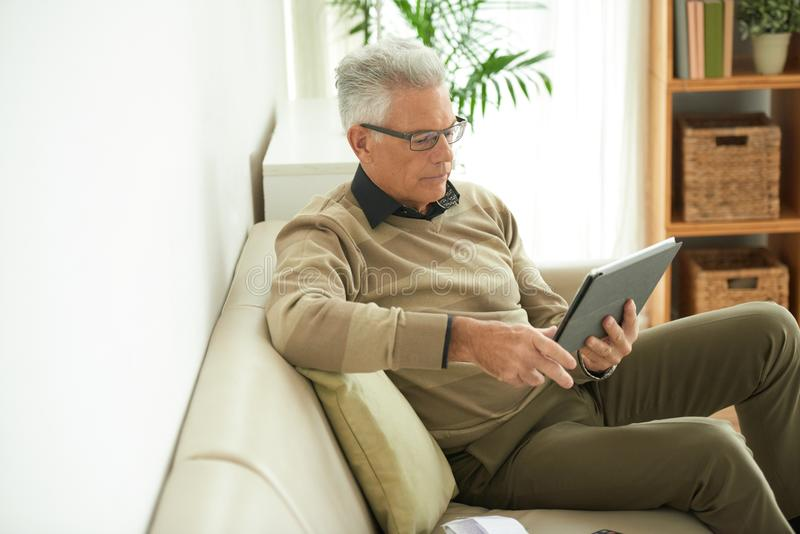 Man reading e-book stock photo