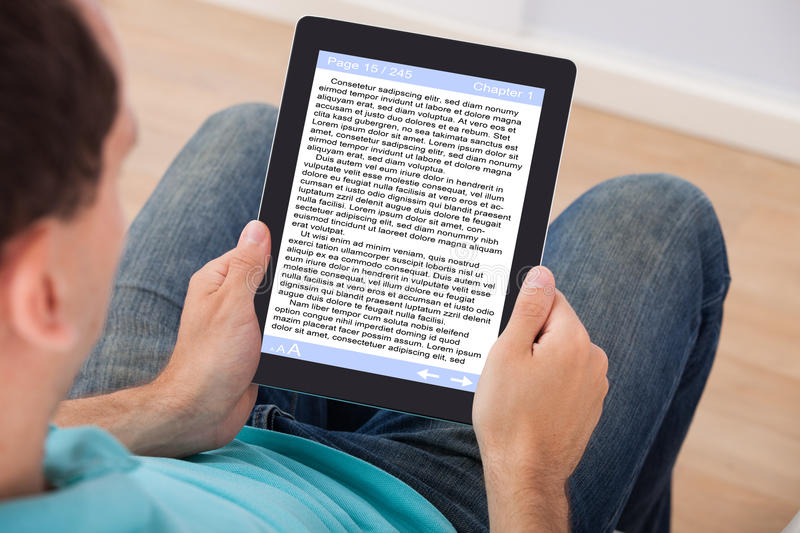 Man reading ebook at home. Man reading eBook on digital tablet at home stock photography
