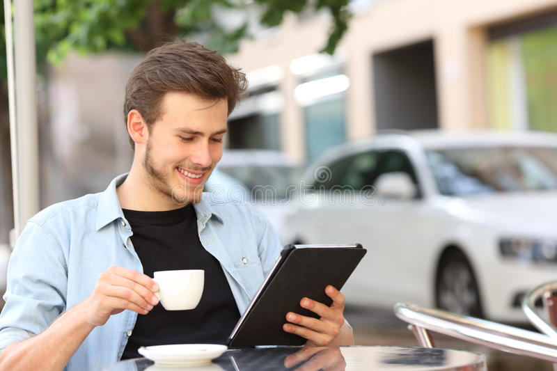Man reading an ebook or tablet in a coffee shop. Happy man reading an ebook or tablet in a coffee shop terrace holding a cup of tea stock photo