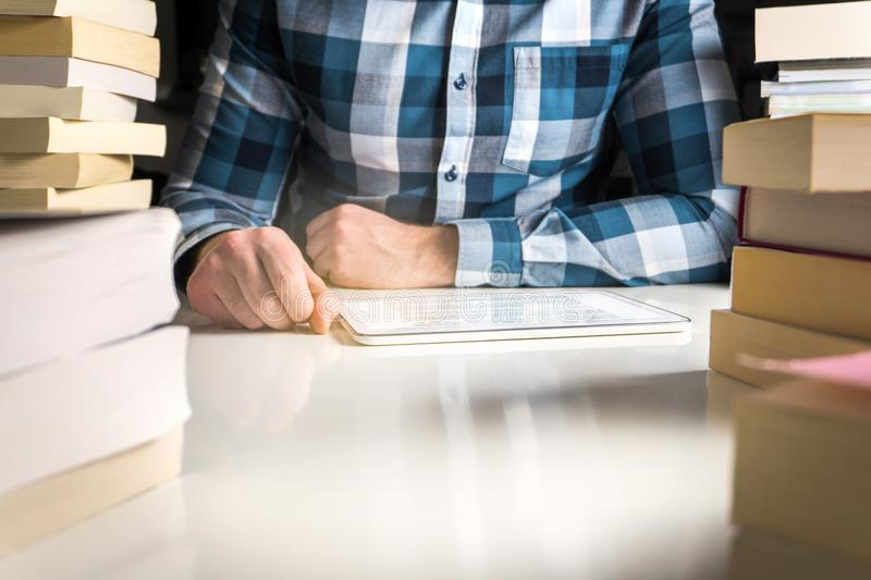 Man reading electronic book or online news with reader. Book in tablet or smart mobile device surrounded by stacks of books stock photos