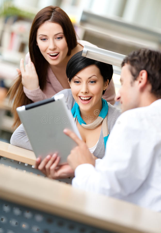 Man at the reading hall shows tablet to two women stock photography