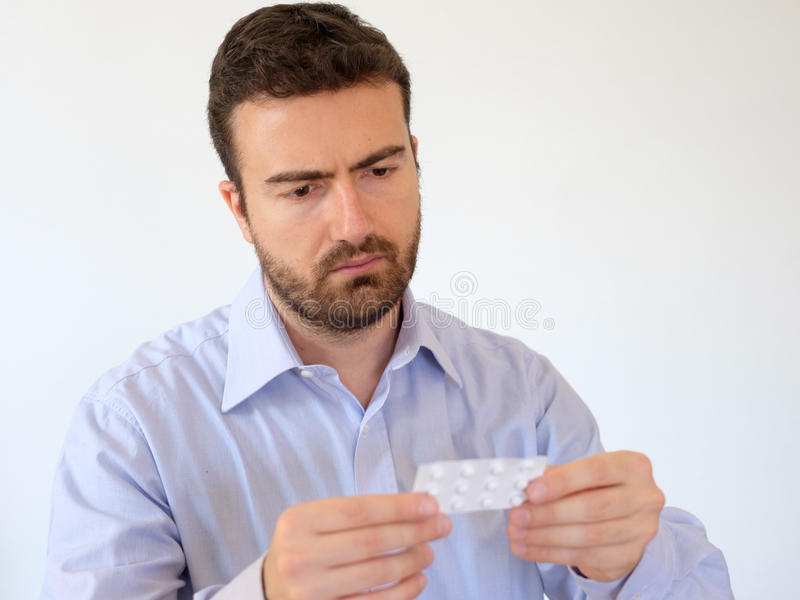 Man reading instructions of a medicine. In his hand royalty free stock photo