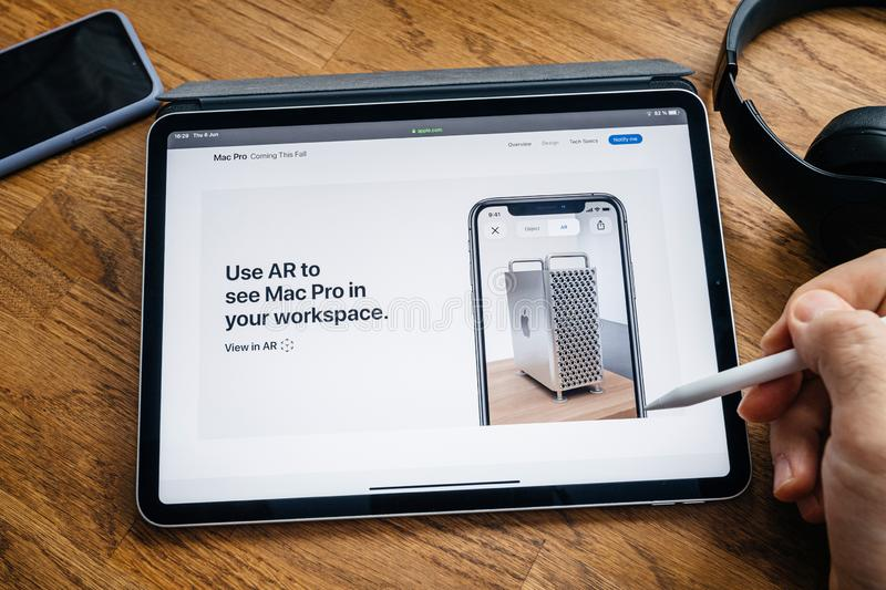 Man reading on iPad Pro launch Mac Pro workstation. Paris, France - Jun 6, 2019: Man reading on Apple iPad Pro tablet about latest announcement of at Developers stock photography