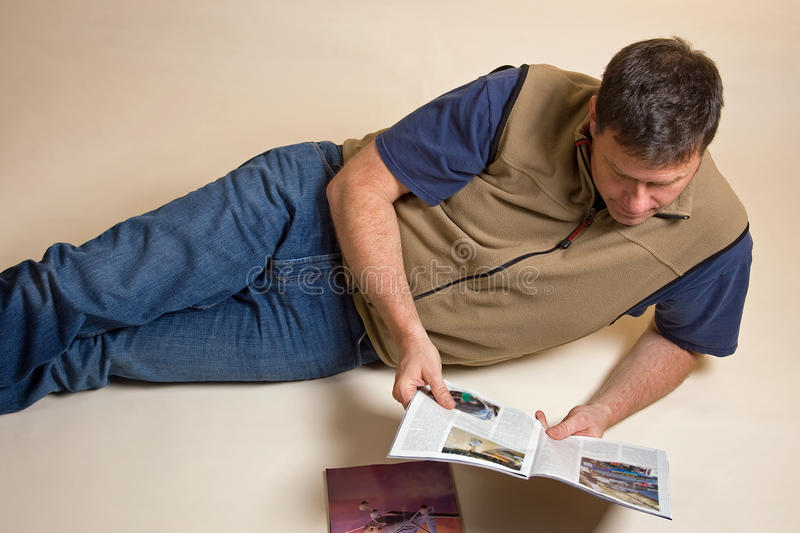 Man reading magazines. Man casually reading magazines neutral background royalty free stock photo