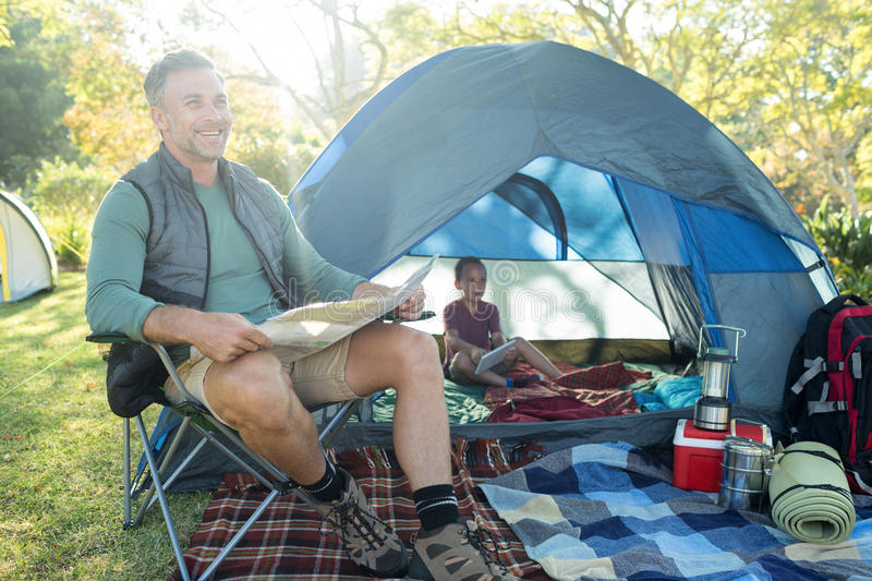 Man reading the map outside the tent at campsite. Smiling man reading the map outside the tent at campsite royalty free stock photos