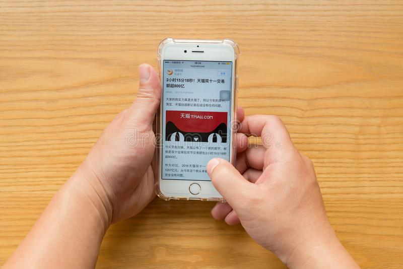 Man reading mobile news saying Tmall sales more than 80-billion RMB in 2 hours 15 minutes 18 seconds in the Chinese online shoppin royalty free stock images