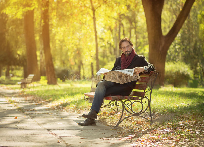 Man reading newpaper in the park royalty free stock image
