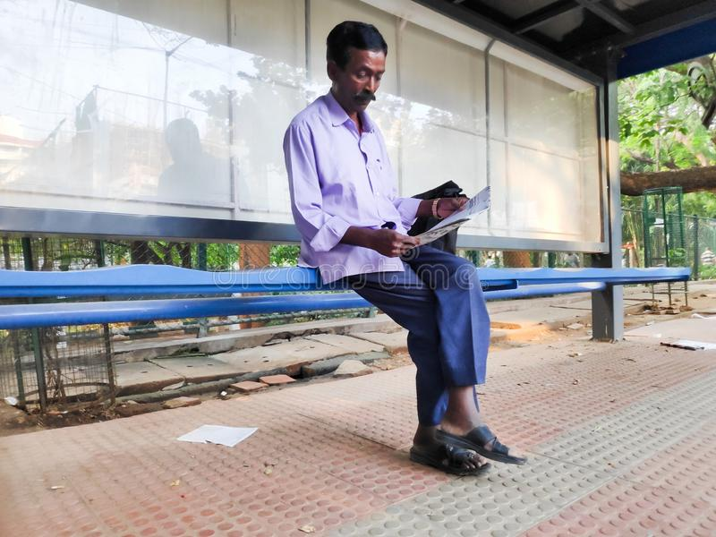 Man reading newspaper in Bangalore, India. Bangalore, India - May 17, 2019 - An Indian man reads a newspaper at a bus stop in Bangalore, India stock image