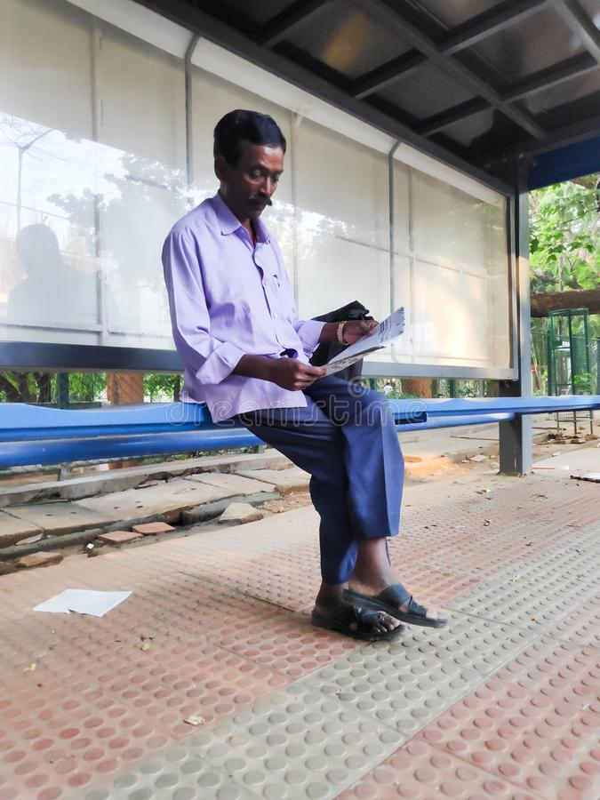Man reading newspaper in Bangalore, India. Bangalore, India - May 17, 2019 - An Indian man reads a newspaper at a bus stop in Bangalore, India stock photography