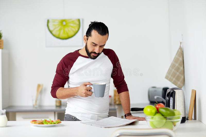 Man reading newspaper and eating at home kitchen. Vegetarian food, healthy eating, people and diet concept - man having vegetable sandwiches with coffee for royalty free stock photo