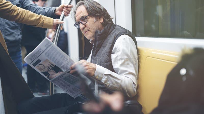 Man reading newspaper in the metro train. Man reading newspaper  in the metro train royalty free stock image