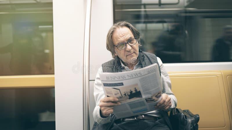 Man reading newspaper in the metro train. Man reading newspaper in  the metro train royalty free stock photos