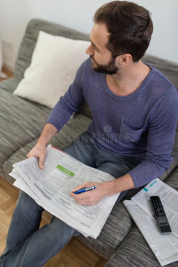 Man reading the newspaper on a sofa royalty free stock image