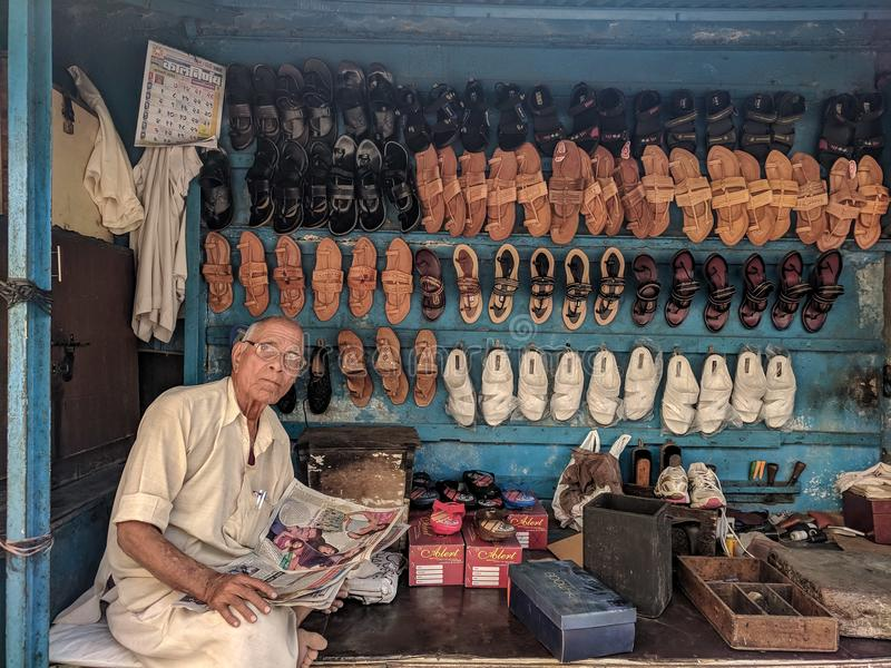 Man Reading Newspaper Surrounded by Shoes royalty free stock image