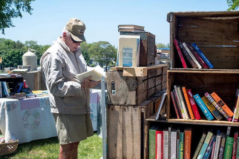 Man reading old books at a book sale in Michigan USA royalty free stock photos