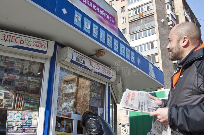 Man is reading the Russian newspaper. Russian news. A man is reading a newspaper. A man is buying a newspaper. What the Russian media say. What do the Russian stock image