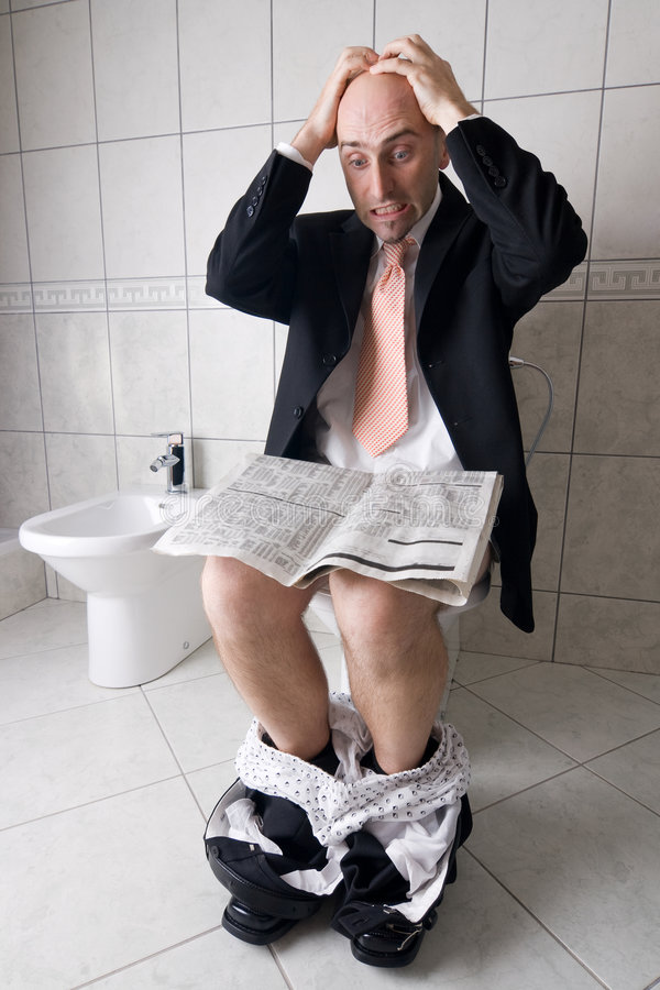 Man reading on toilet. Man reading newspaper on toilet, expressing surprise at what he is reading stock photo