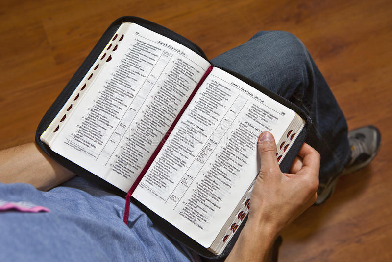 A man reads the Bible. A man holds an open Bible and reads royalty free stock photos