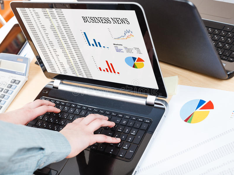 Man reads business news from laptop at office desk. Business workflow - businessman reads business news from laptop at office desk stock image