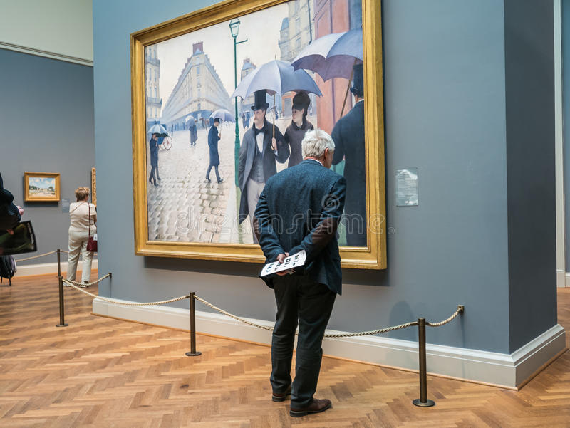 Man reads exhibition label for Caillebotte's Paris Street, Art I royalty free stock photography