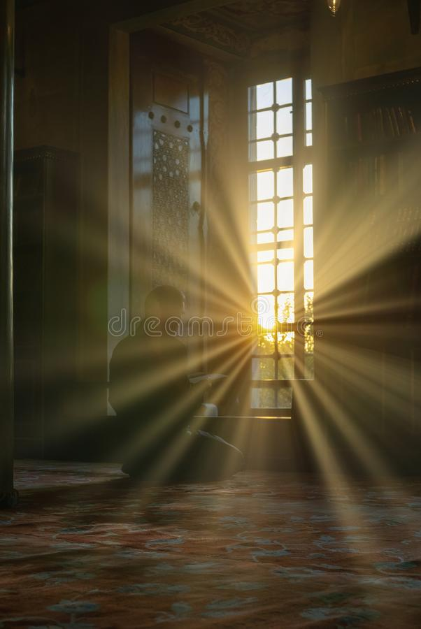 ISTANBUL, TURKEy-SEPTEMBER 24, 2016 :  a man reads Koran or Al Quran with intentional lens flare sun setting up inside Sultanahmet stock photography