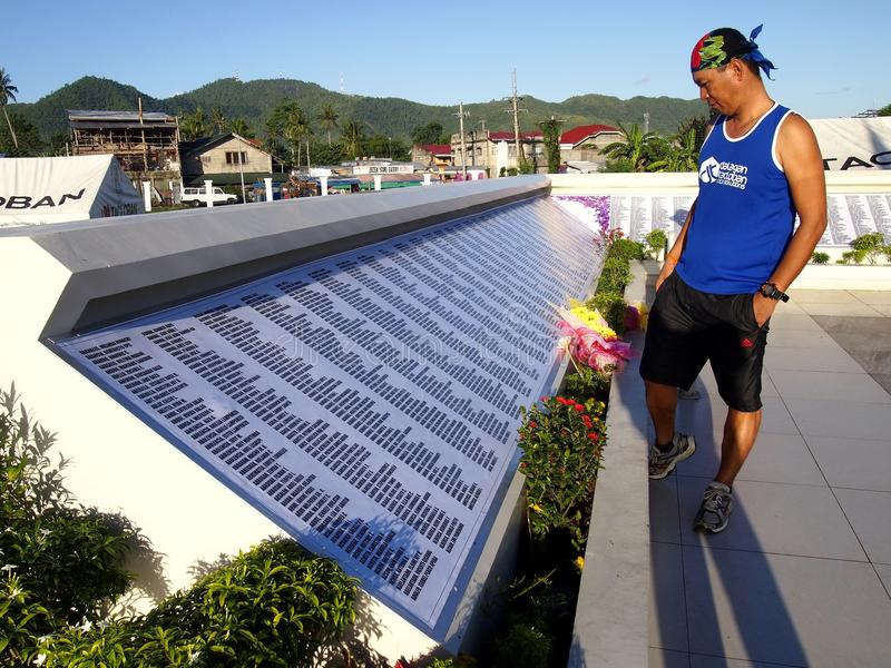 A man reads the names in a monument in remembrance of those who perished in the storm surge brought by typhoon Yolanda. TACLOBAN CITY, PHILIPPINES - NOVEMBER 9 stock photos