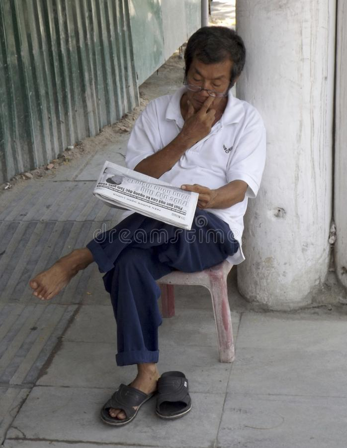 A man reads a newspaper sitting on a chair at the door of his shop. Nha Trang, Vietnam royalty free stock photo