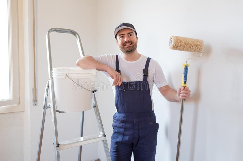 Man ready to paint one wall holding painting tools stock photography
