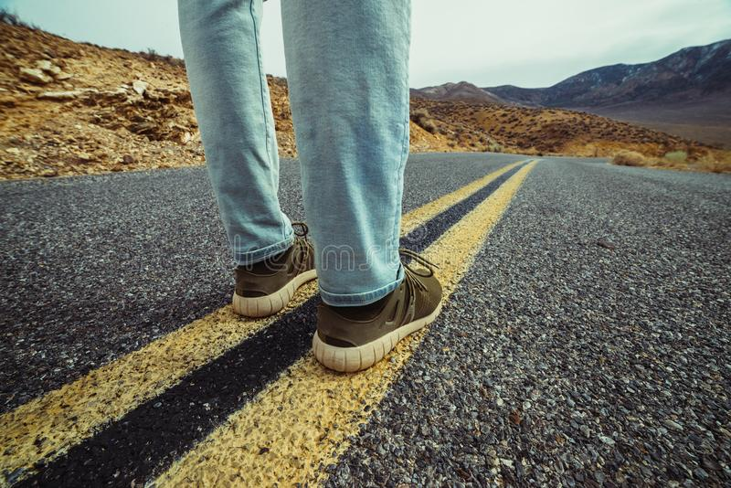 Man ready to take a new way and make a step to new life concept. Feet on empty and free asphalt road in desert. royalty free stock images