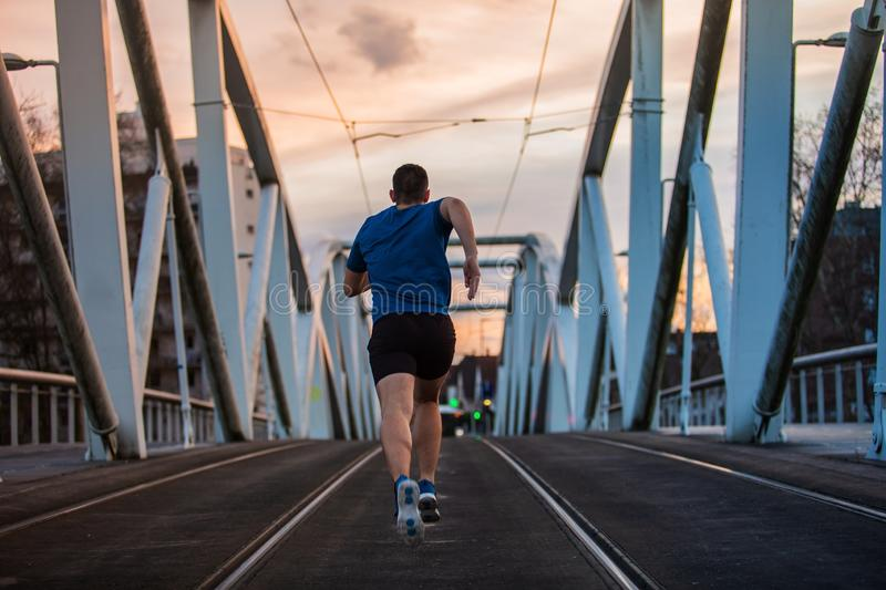 Man rear view running fast along bridge. Athletic man practicing sport outdoors rear view running fast along bridge. Self overcome conquering obstacles and win stock images