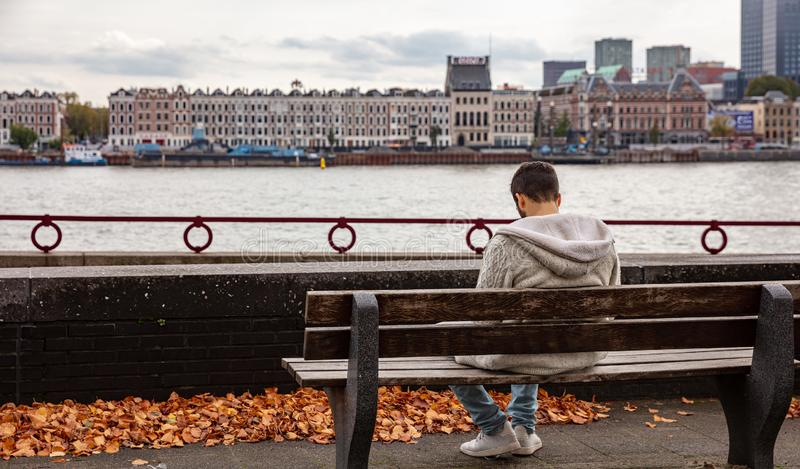 Man rear view sitting on a park bench alone, Rotterdam, Netherlands skyline, cloudy autumn day. Autumn solitude. Man rear view sitting on a park bench alone stock photography