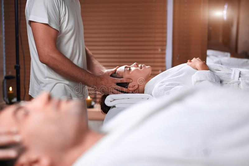 Man receiving back massage from masseur in spa stock images