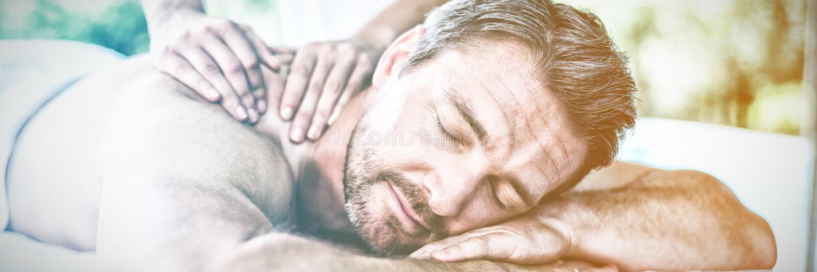 Man receiving back massage from masseur royalty free stock image