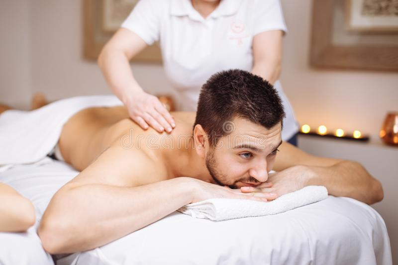 Man receiving back massage from masseur in spa royalty free stock photography