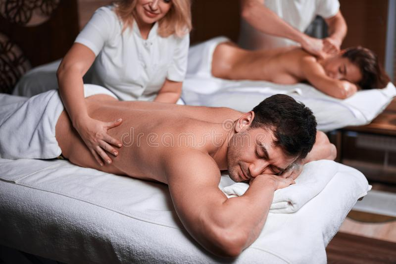 Man receiving back massage from masseur in spa royalty free stock photo