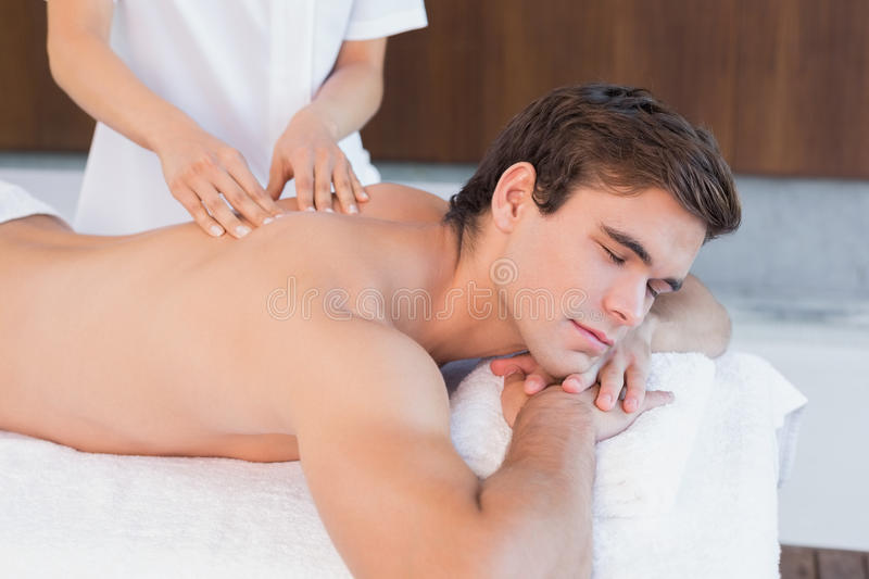 Man receiving back massage at spa center. View of a young man receiving back massage at spa center royalty free stock images