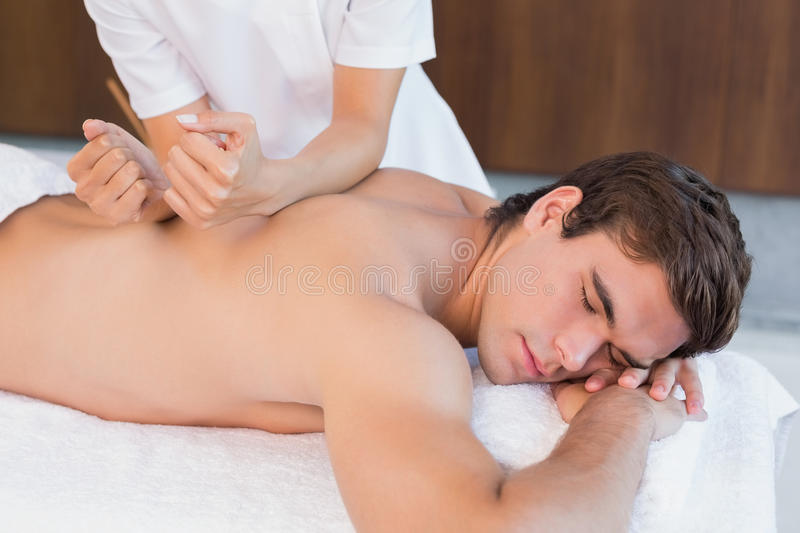 Man receiving back massage at spa center. View of a young man receiving back massage at spa center stock image