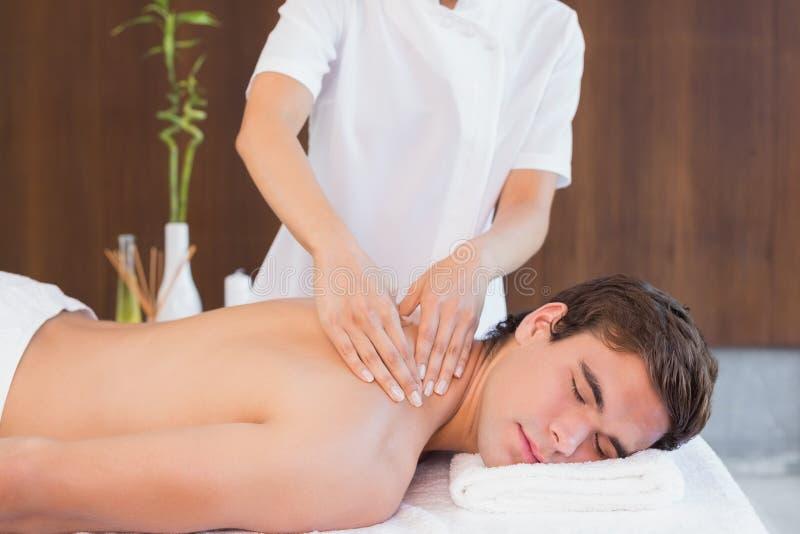 Man receiving back massage at spa center. View of a young man receiving back massage at spa center stock photos