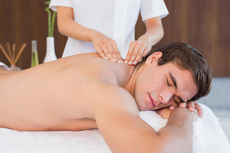 Man receiving back massage at spa center. View of a young man receiving back massage at spa center royalty free stock photo